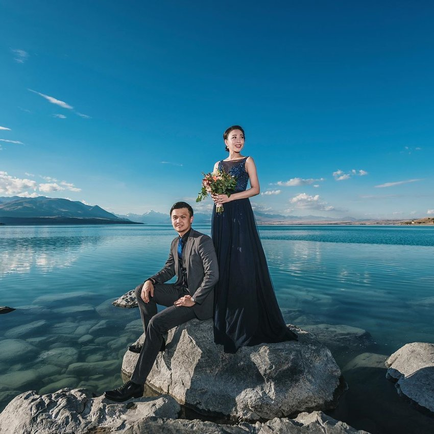 Couple in formalwear doing a photoshoot by the ocean