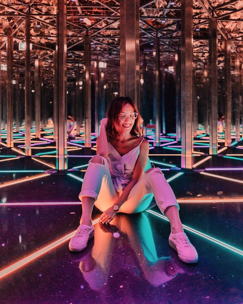 Woman in colourful hall of mirrors