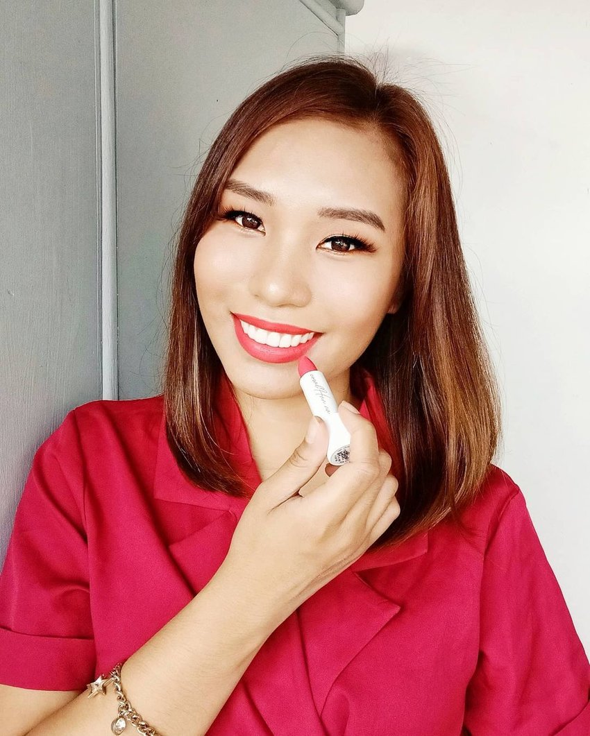 A girl wearing the Jenny House Cosmetics Airlift Lipstick in Coral Han.na