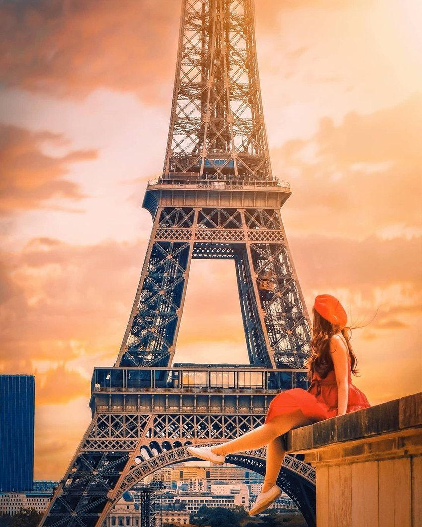 A girl sitting in front of the Eiffel Tower