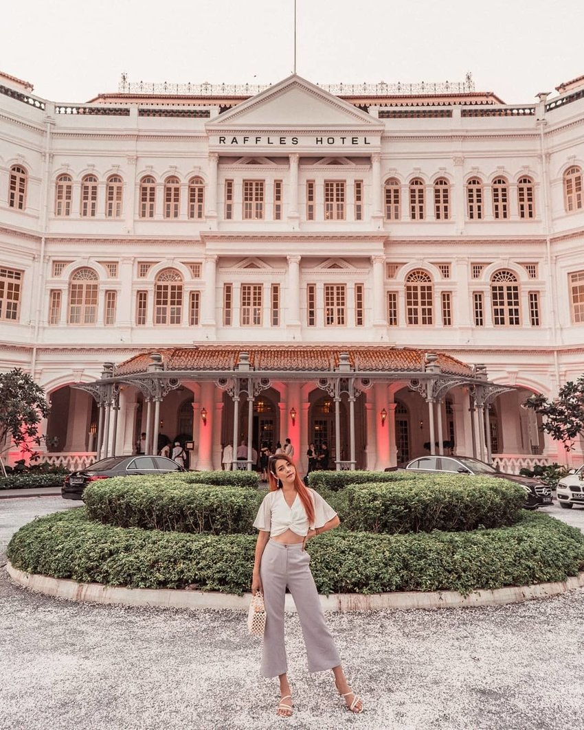 Person posing in front of Raffles Hotel