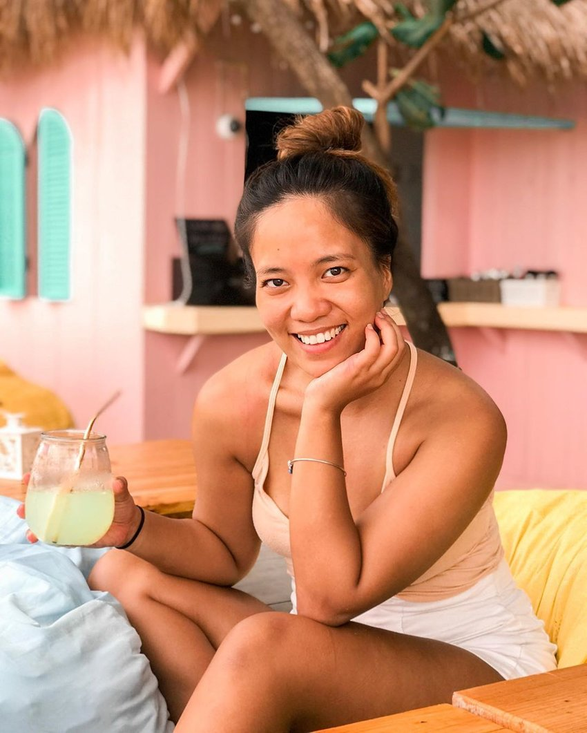 Woman wearing swimsuit sipping on cocktail