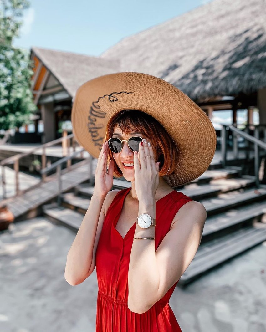 Girl in a red dress wearing a hat and sunglasses