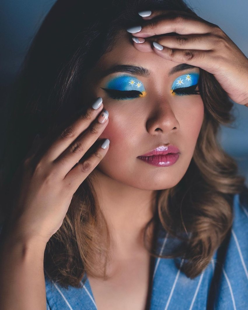 A girl wearing colourful makeup with blue eyeshadow