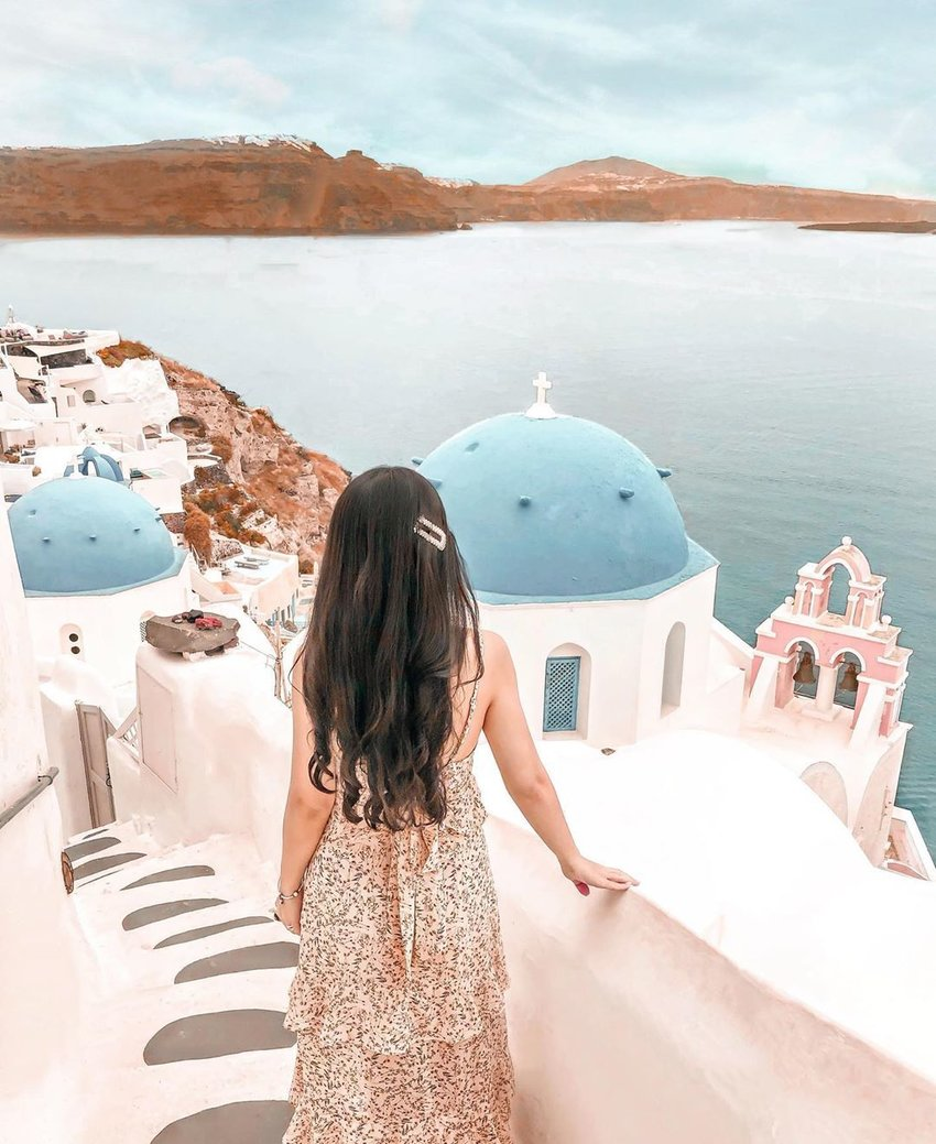 For creative travel photos, take inspiration from this photo of a girl overlooking the sea in Greece